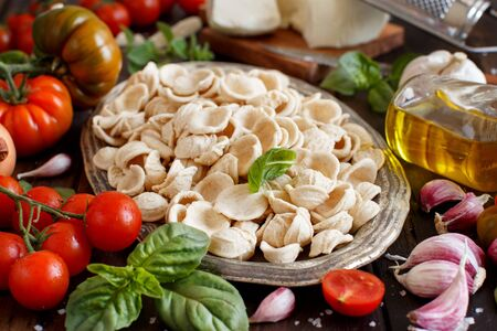 Fresh raw italian pasta orecchiette on a tray, vegetables, herbs and olive oil close up, South Italian food concept