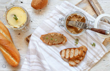 Sandwiches with homemade liver pate and Jar of pate on a table