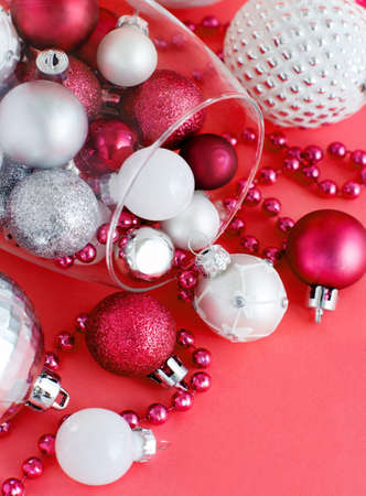 Christmas baubles in a wine glass on red background close up Stock Photo