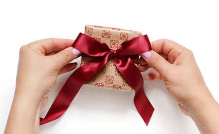 Hands tie a ribbon bow on anEcru gift box on white top view Zdjęcie Seryjne