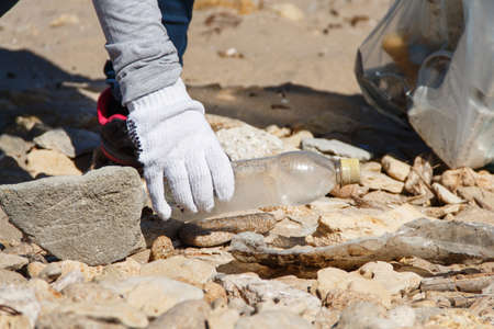 Young woman cleaning beach area from plastic bottles close up 版權商用圖片