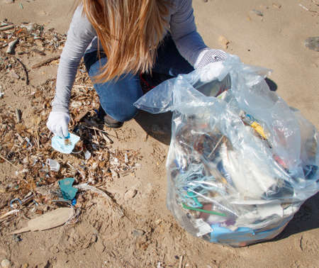 Young woman picking surgical mask during cleaning beach area 版權商用圖片