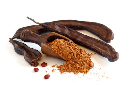 Dry carob powder in a scoop and pods close up isolated on white 版權商用圖片