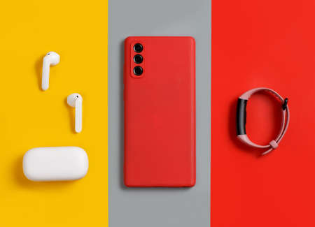 Smartphone, white wireless earphones awith the case and smart watch top view on red, grey and yellow background Banque d'images