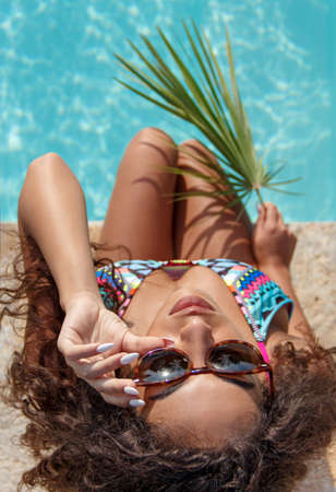 Top view of Young caucasian woman in one-piece swimsuit with tropical leaf near a swimming pool top view Banque d'images