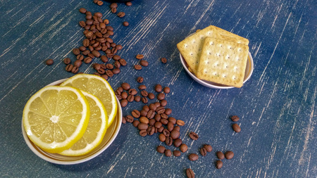Breakfast items such as coffee beans, lemon slices and crackers are prepared on the table