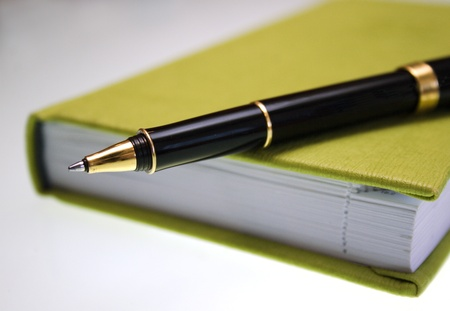 Green notebook and pen photo