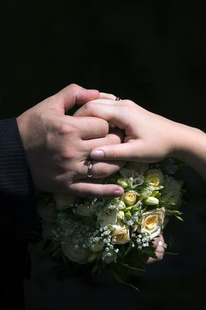 Hands with rings on a wedding bouquet on a black background photo