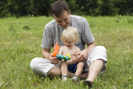 The father plays with the child in park photo