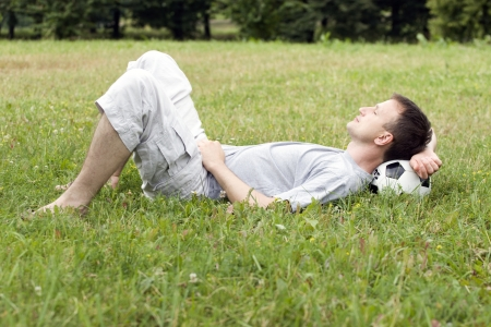 Young man lying on the grass with soccer ball  photo