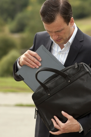 incorporates: businessman gets the laptop from a business bag. Business concept