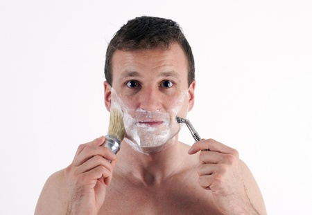 The young man with accessories to shaving.  Isolated on a white background  photo