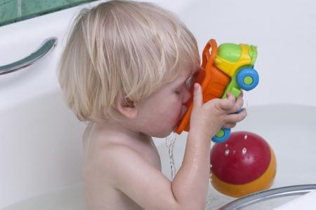 Schattige kleine jongen baden met speelgoed