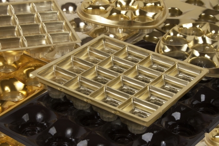 out of production: empty golden boxes of chocolates shapes background