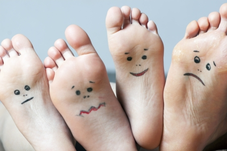 dirty feet: Close up of human soles with smiles Stock Photo