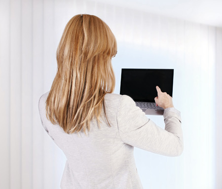 Woman with laptop from a back photo