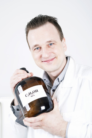 Man holds  large bottle with  written formula of alcohol. photo