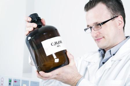 Man holds  large bottle with  written formula of alcohol. photo