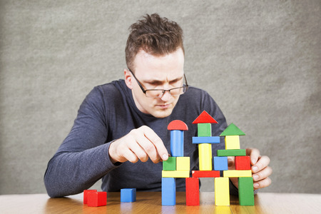 swindler: Man builds the house of childrens toy blocks