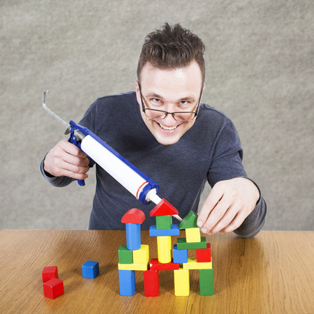 swindler: Man glues house from cubes by construction gun Stock Photo
