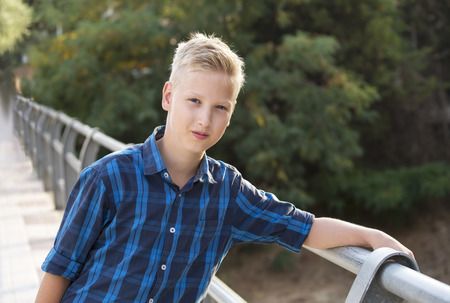 boy 12 year old: Boys portrait in a blue shirt on the bridge Stock Photo