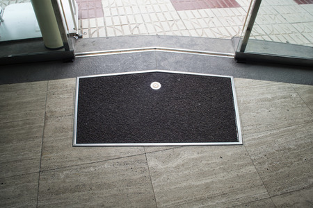 welcome mat: Black with metal frame mat on the gray stone floor near metal glass sliding door