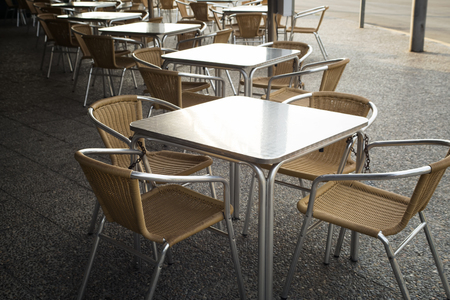 metall and glass: Metal rattan empty tables and chairs outdoor of restaurant. Front view. Have a place for text.