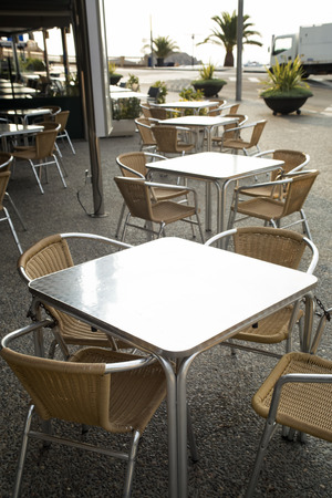 Metal rattan empty tables and chairs outdoor of restaurant. Front view. Have a place for text.