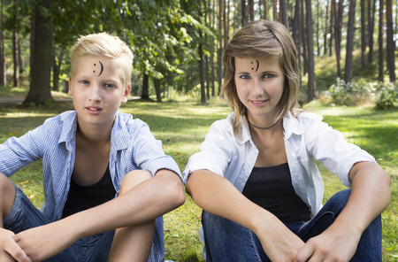 siblings: Concept of positive thoughts and emotions. On the forehead shows (drawn) smile icon. Smiling boy and girl (siblings) are sitting on green grass in nature sunny day.