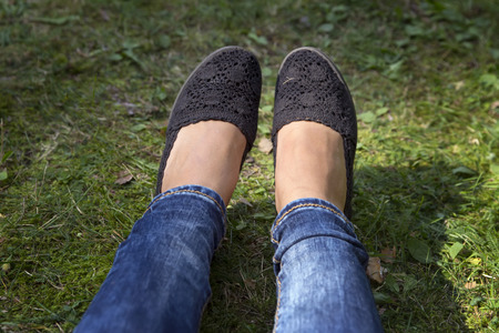 court shoes: Girl lying alone on green grass lawn in summer park. Black court shoes close-up.