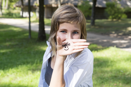 gasp: Smiling girl in nature sunny day. On the palm shows (drawn) smile icon. Concept of positive thoughts and emotions.