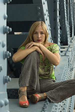 Young blonde urban woman in casual clothes seats on the bridge.  Outdoor portrait