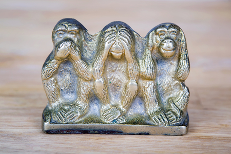 detachment: Souvenir figurines of the three monkeys, symbolizing the Buddhist idea of non-doing of evil, detachment from false - see nothing, hear nothing, say nothing, isolated on wooden surface.