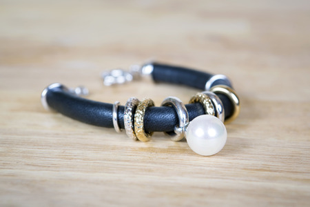 jewelle: Bracelet with pearl, gold and black leather. Jewelry minimalism style. Isolated on wooden surtface.
