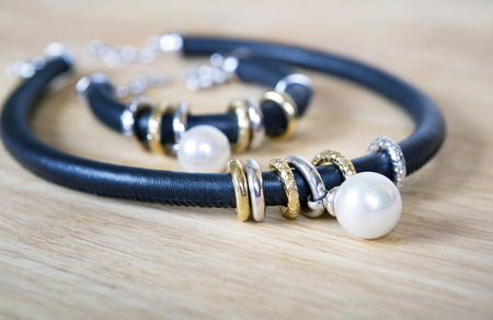 jewelle: Black leather necklace and bracelet with pearl, gold. Jewelry minimalism style. Isolated on wooden surtface.