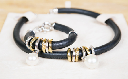 Necklace and bracelet with pearl, gold and black leather. Jewelry minimalism style. Isolated on white surtface. Stock Photo