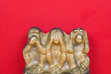 detachment: Souvenir figurines of the three monkeys, symbolizing the Buddhist idea of non-doing of evil, detachment from false. See nothing, hear nothing, say nothing. Isolated on red background. Stock Photo
