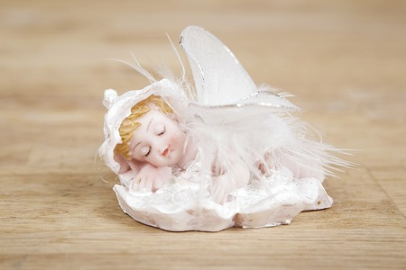weeping angel: Miniature statue of a white little cute angel with featgers wings on wooden surface.