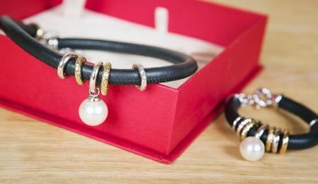 jewelle: Necklace and bracelet with pearl, gold and black leather. Jewelry minimalism style. Isolated on red fashion box. Stock Photo