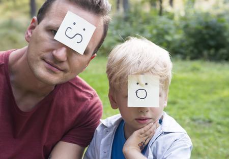 surprise face: Concept of positive thoughts and emotions. On the foreheads shows (drawn) worry and surprise icons. Worried father and surprising son sitting on the green grass in nature sunny day. Stock Photo
