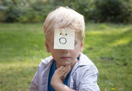 gasp: On the forehead shows (drawn) gasp icon on yellow stickers. Concept of surprise thoughts and positive emotions. Surprising boy sits on green grass in a forest. Stock Photo