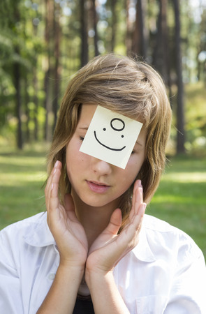 gasp: On the forehead shows (drawn) angel icon on yellow stickers. Concept of positive thoughts and emotions. Smiling girl in nature sunny day.
