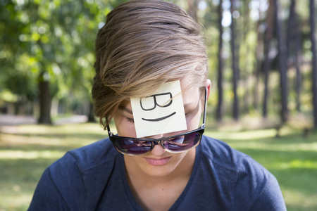 cool backgrounds: On the forehead shows (drawn) cool icon on yellow stickers. Concept of positive thoughts and emotions. Cool boy is sitting on green grass in nature. Stock Photo