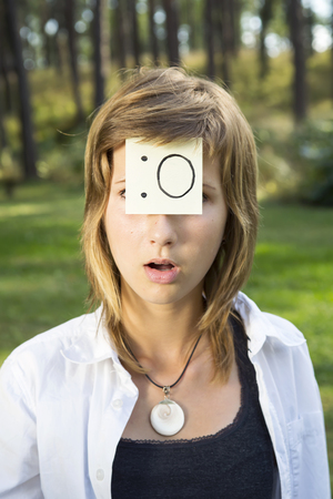 gasp: On the forehead shows (drawn) gasp icon on yellow stickers. Concept of positive thoughts and surprise emotions. Surprised girl in nature sunny day.
