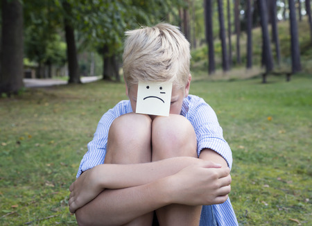gasp: On the forehead shows (drawn) cry icon on yellow stickers. Concept of sad thoughts and negative emotions. Crying boy sits on green grass in a forest. Stock Photo