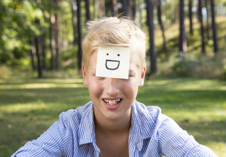 gasp: Concept of positive thoughts and emotions. On the forehead shows (drawn) big grin icon on yellow stickers.  Grining boy is sitting on green grass in nature. Stock Photo