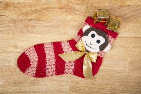 next year: Christmas red sock with monkey and any gold gifts isolated on wood surface, next year symbol like a christmas background.