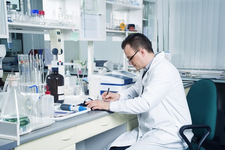 observations: Male lab worker with glasses and white coat with pencil writing down observations in laboratory.