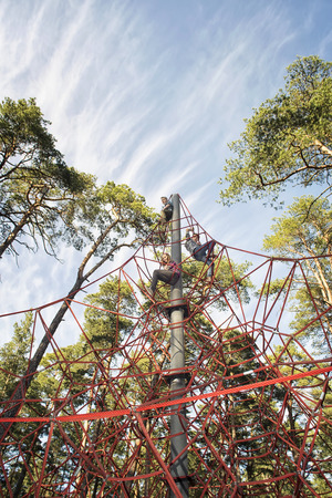 jungle gym: Red jungle gym ropes against blue cloudy sky in a park. Network game for children to climb.