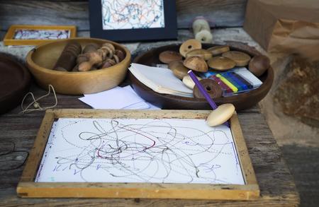 perinola: Perinola de madera sobre tabla de madera con la hoja de papel blanco. L�piz inserta en la perinola de madera. Tal perinola, spinning, dibujo en papel. Juego ni�os letones tradicionales en tiempos antiguos. Foto de archivo